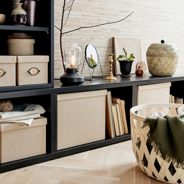Black storage unit, with several beige boxes inside and a lamp and basket on top.