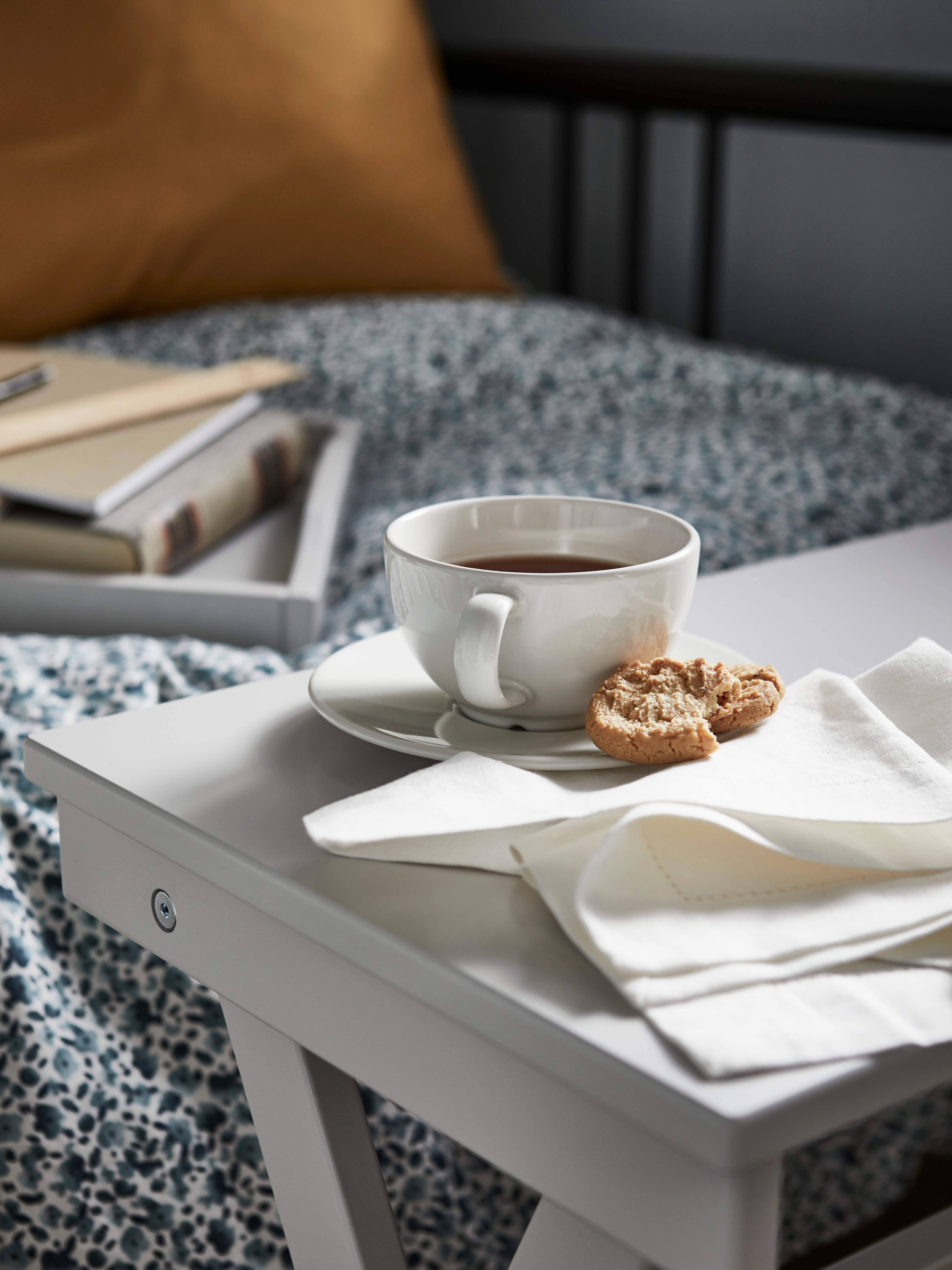 A VARDAGEN off-white teacup with saucer holds tea and a biscuit. It sits on a grey tray table with a fabric tablecloth.
