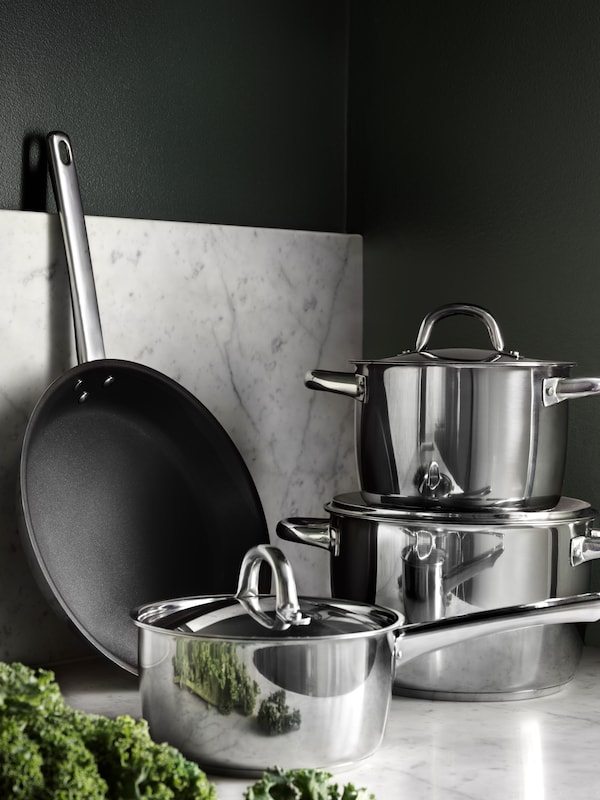 stack of OUMBÄRLIG 7-piece cookware sat on a marble work surface.