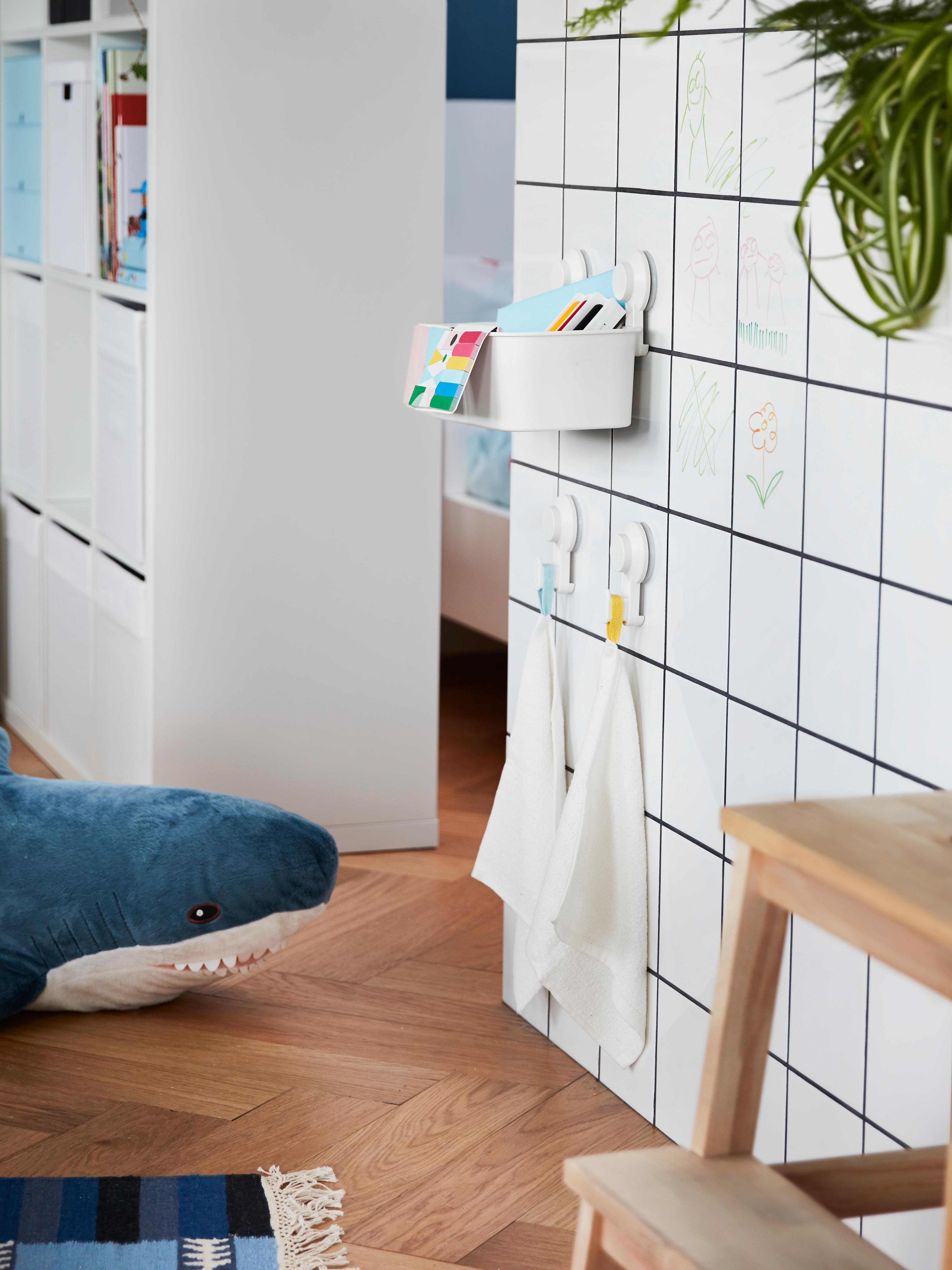 Cestello con ventosa TISKEN su una parete di piastrelle bianche, in una stanza bianca con pavimento in parquet.