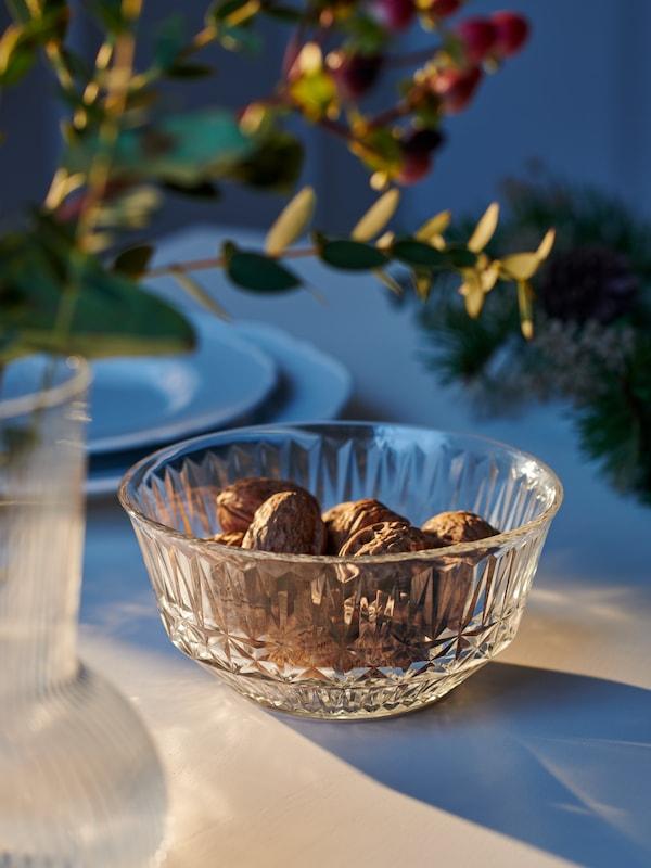 سطح طاولة أبيض عليه ثمار الجوز في سلطانية صغيرة SÄLLSKAPLIG من الزجاج الشفاف عليه رسوم بجوار مزهرية PÅDRAG بها أغصان مورقة.