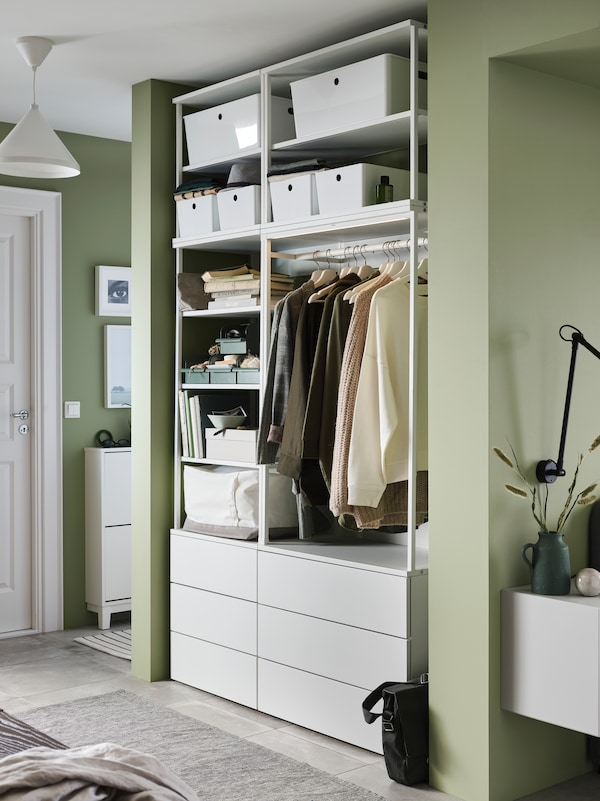 A white PLATSA open wardrobe, with clothes hanging from a rail, shelves with boxes on them, and drawers, stands in a hall.