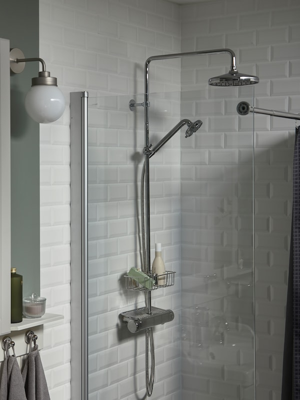A white-tiled shower with a glass door, a chrome-plated VOXNAN head shower and shelf holding two shower products.