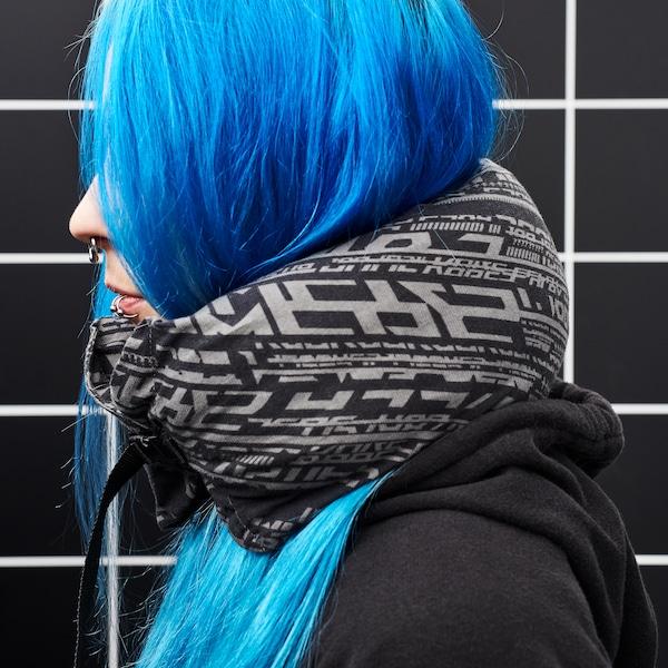 En pige med langt blåt hår står med en nakkepude, som også kan monteres på en gamerstol