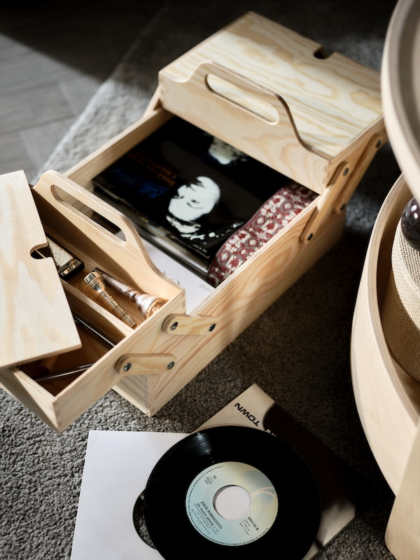 Wooden box on the floor, open. Inside a photograph of a woman, and several objects. Beside a vinyl CD.
