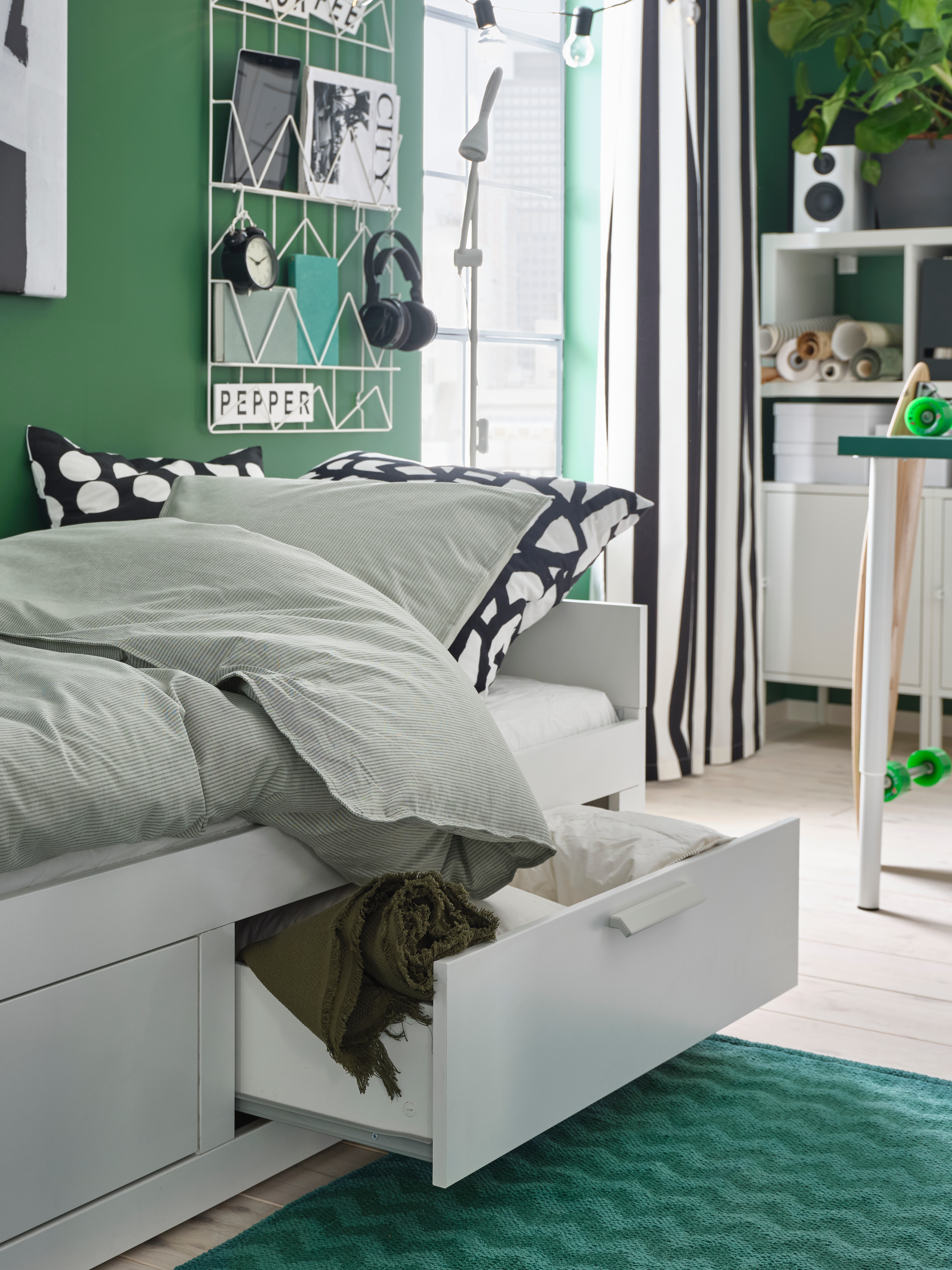 Bedroom with green walls, green rug, white day bed with two drawers, white storage unit and floor lamp.