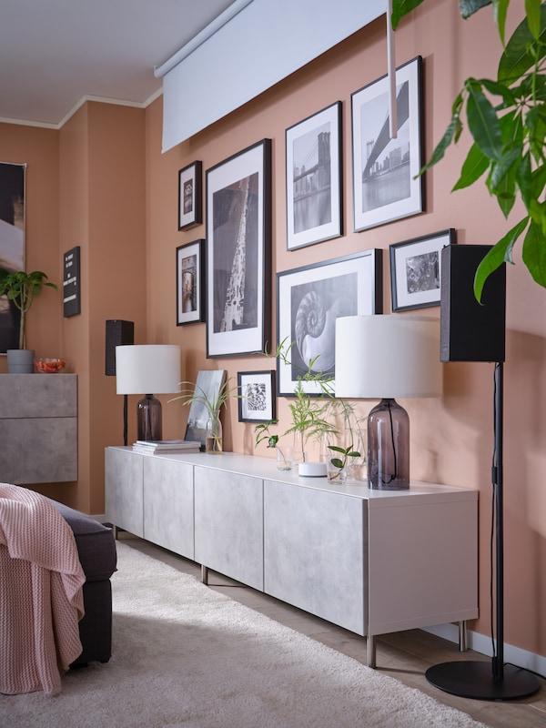 Et tv-bord med låger, indrammet kunst, et mørklægningsrullegardin og to wi-fi-højttalere på gulvstativer.