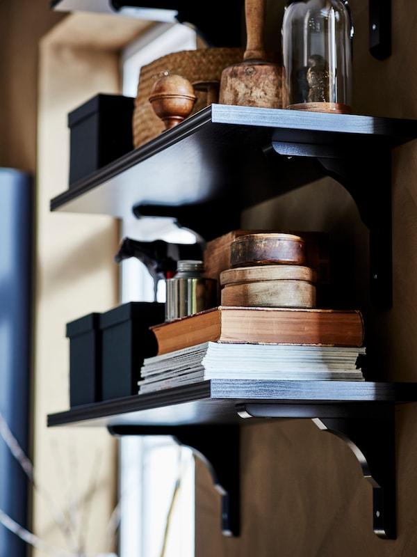Două polițe de perete BERGSHULT/RAMSHULT cu cărți, cutii, ornamente și alte lucruri pe ele sunt montate pe un perete.
