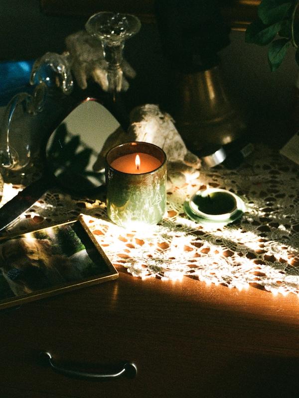 Eine OSYNLIG Duftkerze im Behälter steht auf einem Holztisch. Verschiedene Gegenstände werden beleuchtet, u. a. ein Bilderrahmen.