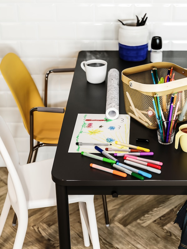 Sedia junior bianca, sedia giallo scuro e tavolo antracite sul quale ci sono pennarelli e matite, fogli di carta e un cestino verde oliva chiaro.