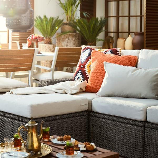 Un banco tapizado en blanco en el exterior, con cojines blancos y naranjas.