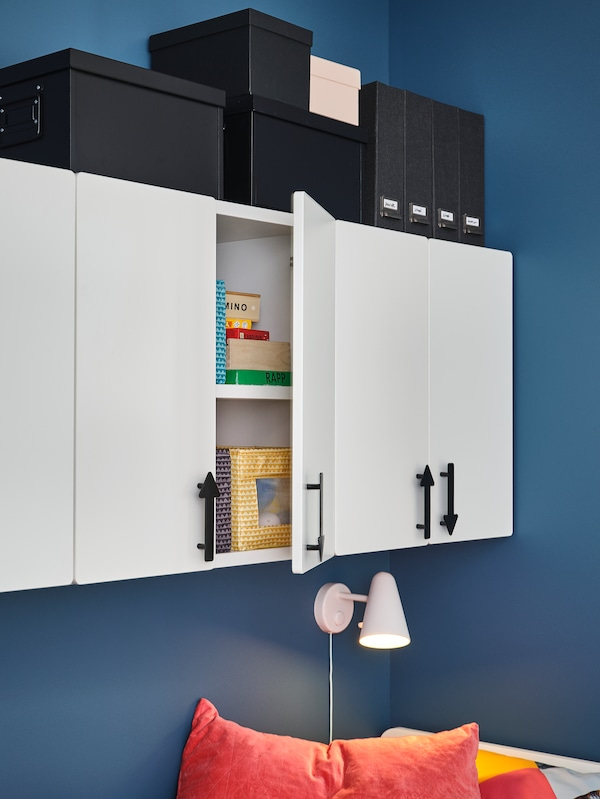 SMÅSTAD cabinets with JÄRNSPARV handles are mounted on a blue wall, and different boxes and magazine files sit on top.