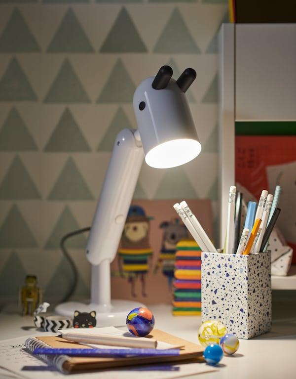 Включенная светодиодная рабочая лампа для детской КРУКС белого цвета стоит на письменном столе рядом с канцелярскими принадлежностями и стеклянными шариками.
