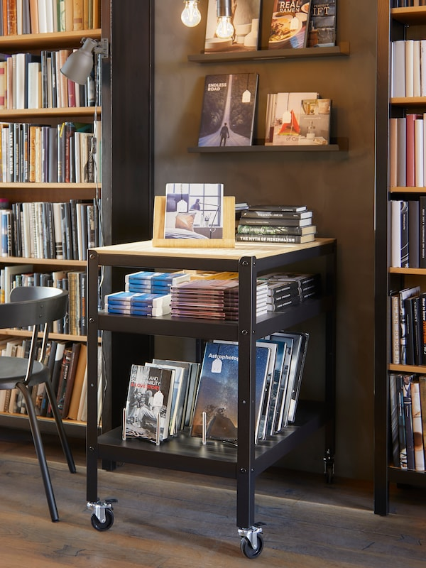 A table with books on display, both on top and on the lower level, bookcases behind, and shelving with books.