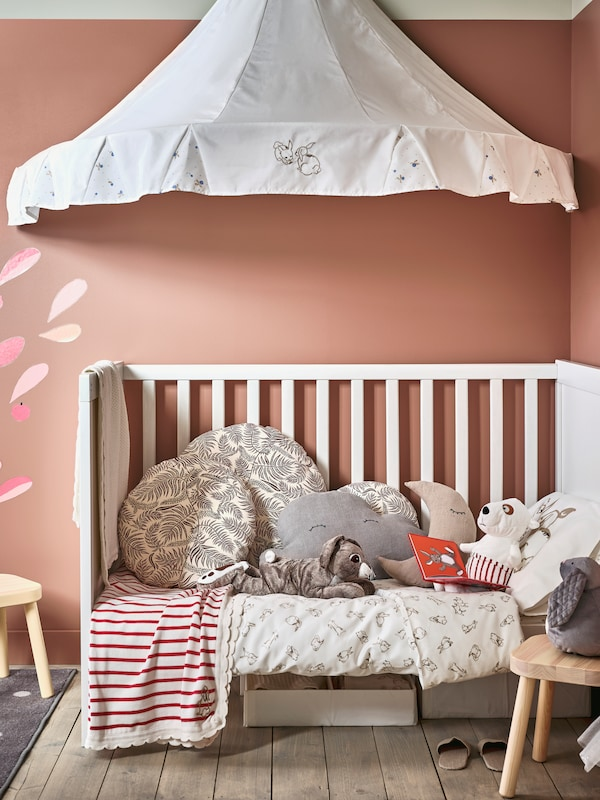 A white SUNDVIK cot made with RÖDHAKE bed linen, blankets, cushions and soft toys, with a canopy above.
