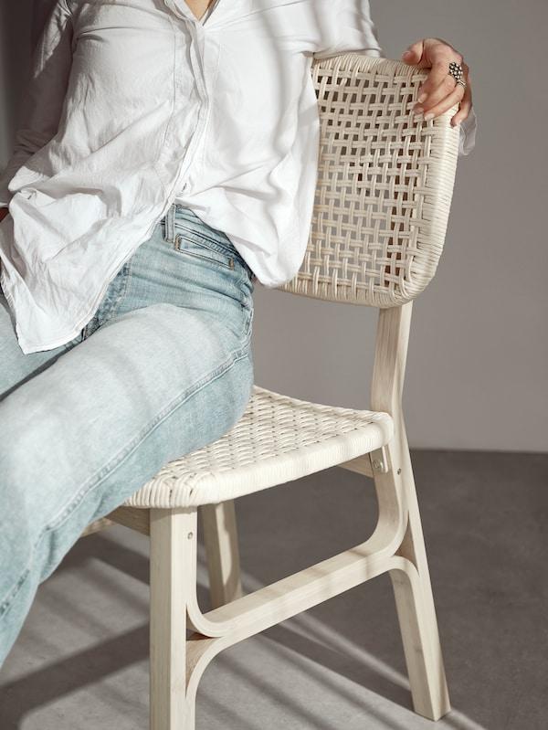 Kobieta ubrana w białą koszule i jeansy siedząca na krześle VOXLÖV z jasnego bambusa.