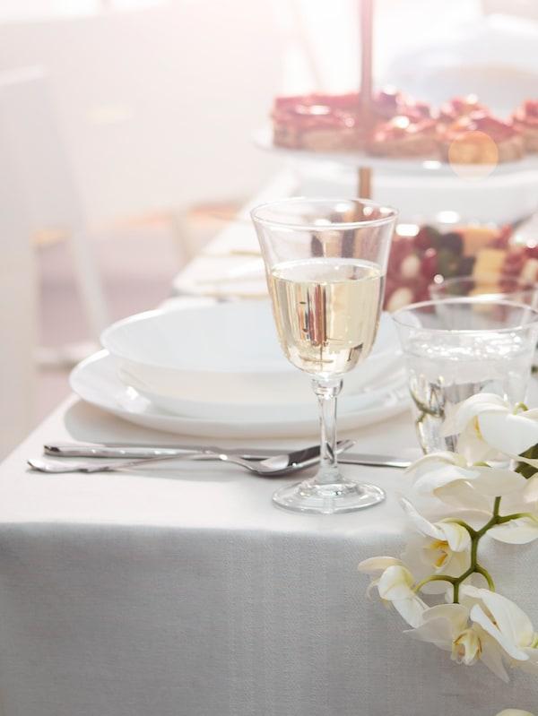 Tigela branca com mirtilos em cima de um prato de sobremesa branco num prato maior STRIMMIG cinzento.