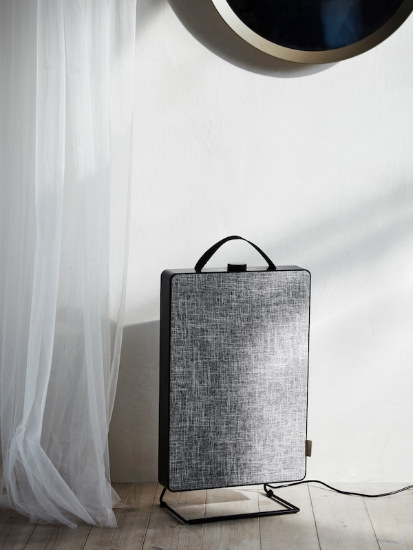 A black and grey FÖRNUFTIG air purifier stands on a wooden floor, next to a transparent white curtain.