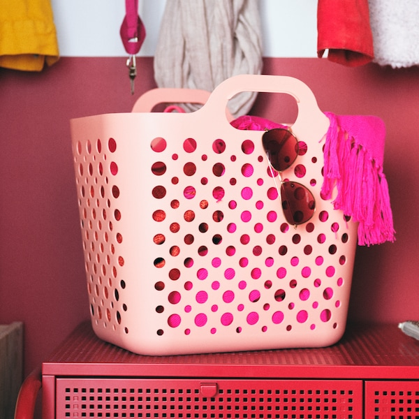 A pink SLIBB flexible laundry basket holding accessories stands on a red NIKKEBY four-drawer chest of drawers.