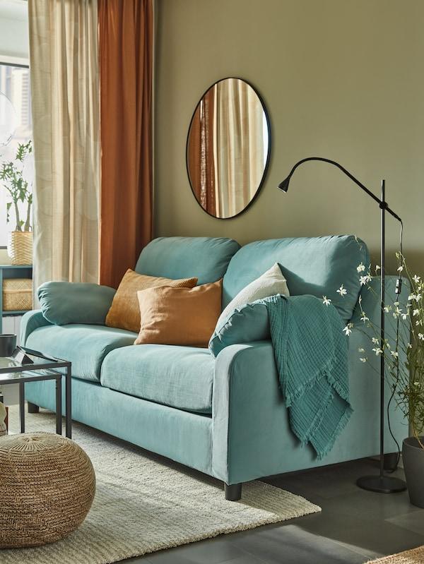 Світло-бірюзовий диван із високою спинкою біля стіни болотяного кольору, кругле дзеркало, темно-бежеві подушки, чорний світильник для читання.