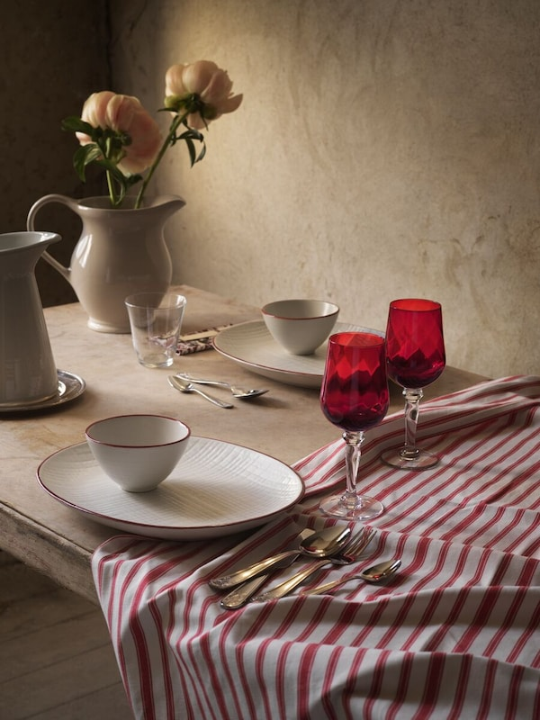 A table with a VINTER 2020 red and white striped tablecloth, 2 red VINTER 2020 wine glasses, a jug and dinnerware on it.