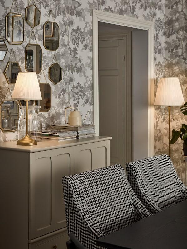 당초무늬 벽지가 발려진 우아한 응접실에 오르스티드 스탠드와 탁상 스탠드가 밝혀져 있는 모습.