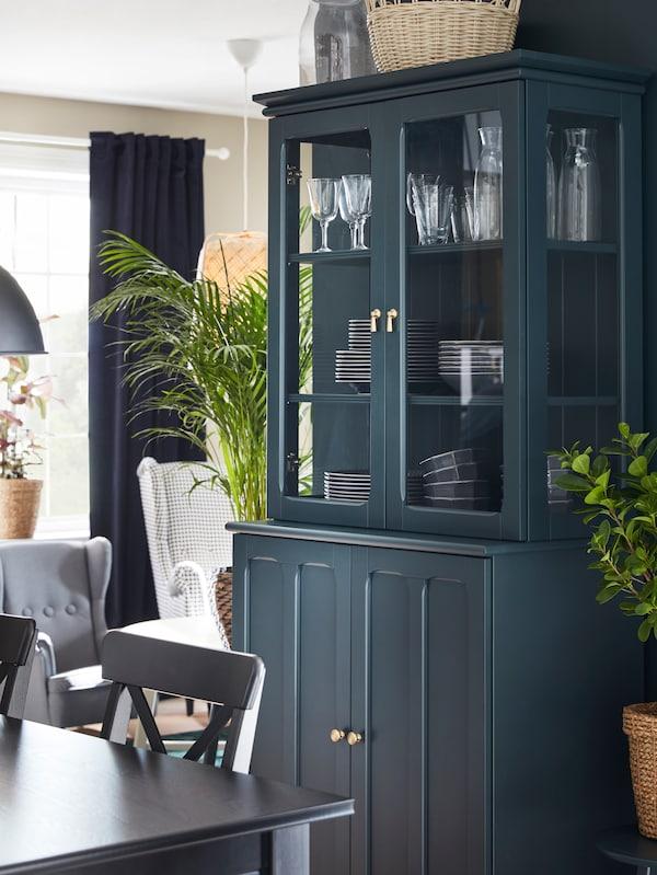 Un corp LOMMARP bleumarin-verde cu uși de sticlă este amplasat alături de o masă. În spatele ușilor de sticlă se vede veselă.
