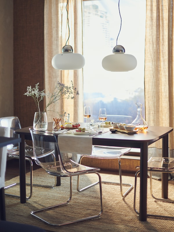 A STRANDTORP extendable table in front of a large window, laid for a meal for two with flowers, food dinnerware and glasses.
