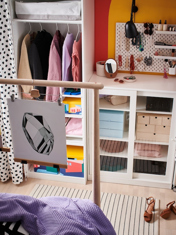 Storage stands along a wall, including a SYVDE cabinet with glass doors and a wardrobe frame, with clothes and boxes.