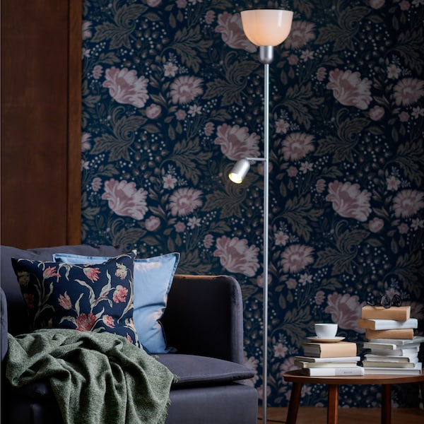 Dark living room with a tall HEKTOGRAM standing light, floral wall paper and matching floral cushion