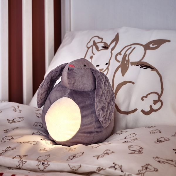 A rabbit-shaped PEKHULT soft toy with LED night light sits in a white SUNDVIK crib with RÖDHAKE bed linen.