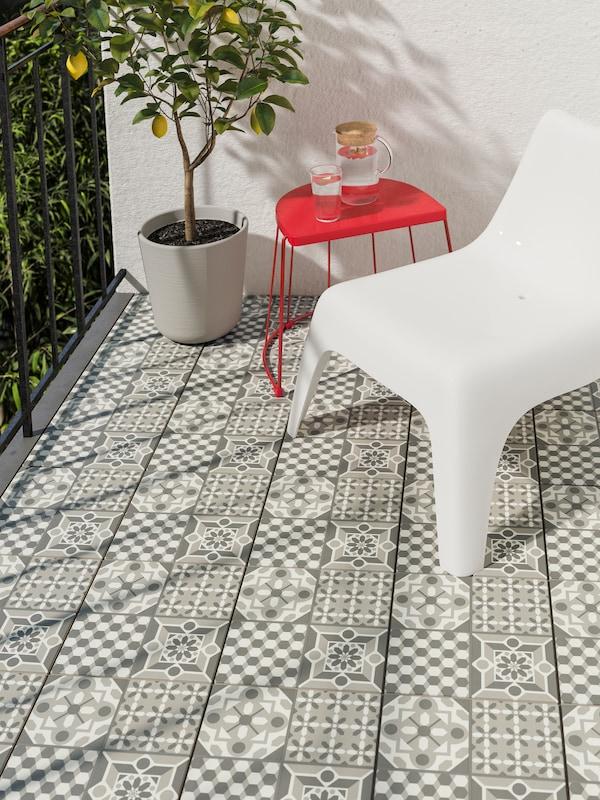 Una silla de plástico de exterior blanca con una mesa de exterior en rojo y una planta en una maceta, todo ello en un balcón con un suelo de diseño.