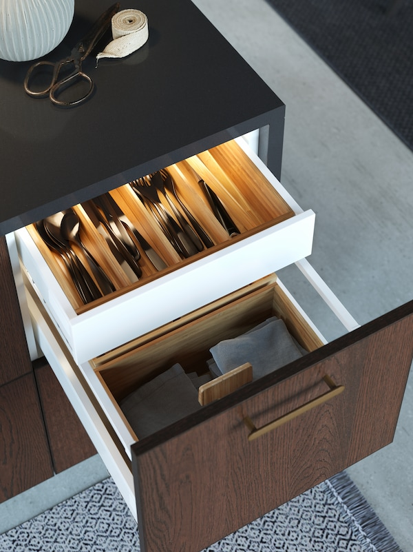 Open drawers on the kitchen island revealing neat wooden trays with cutlery and integrated lighting.