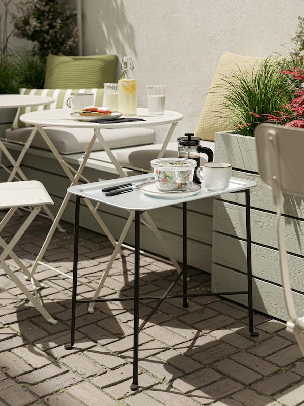 Tavolino vassoio con vassoio azzurro e gambe nere, sul quale sono appoggiati una ciotola di insalata, caffè e posate.