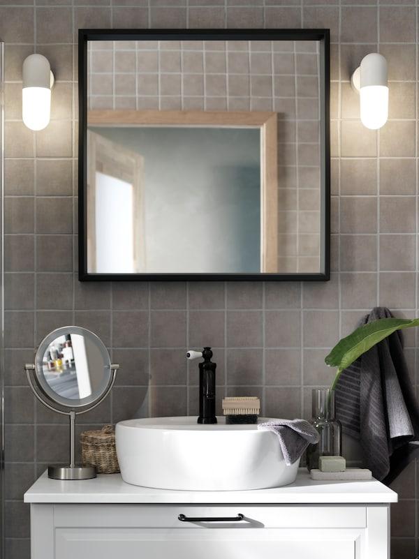 Zwei eingeschaltete ÖSTANÅ Wandleuchten seitlich eines NISSEDAL Spiegels in einem beige eingerichteten Badezimmer mit einem weißen Waschbeckenschrank.