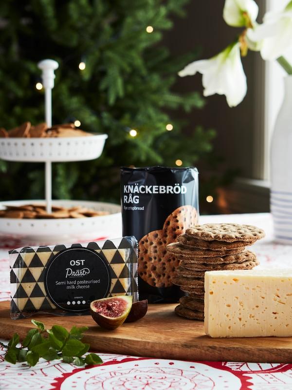 Drevená doska na krájanie so syrom a s hŕbou chrumkavého chleba, na obruse je vianočný červeno-biely vzor.