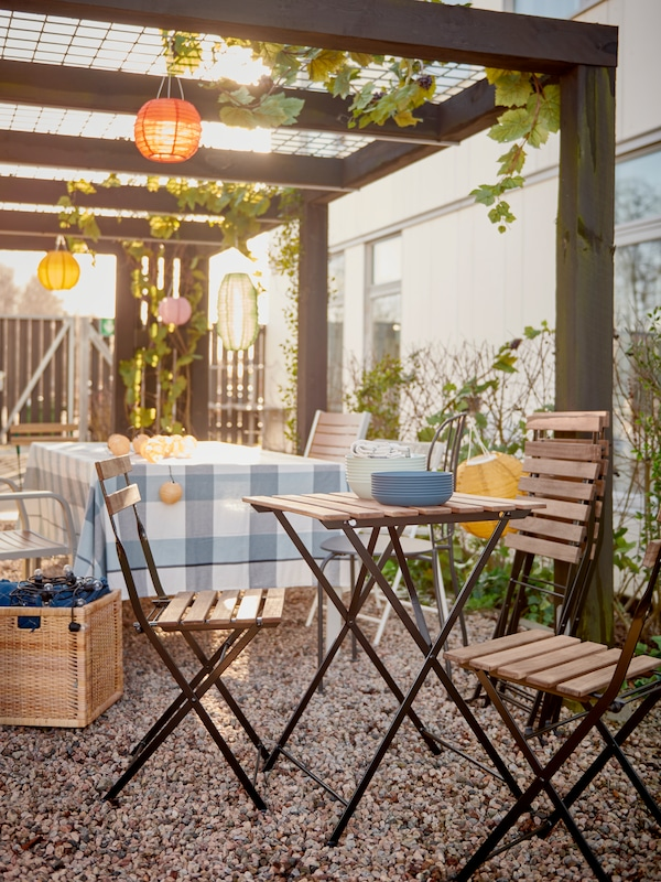 Chairs and small tables set for a party under a decorated pergola in a courtyard with hanging lamps.