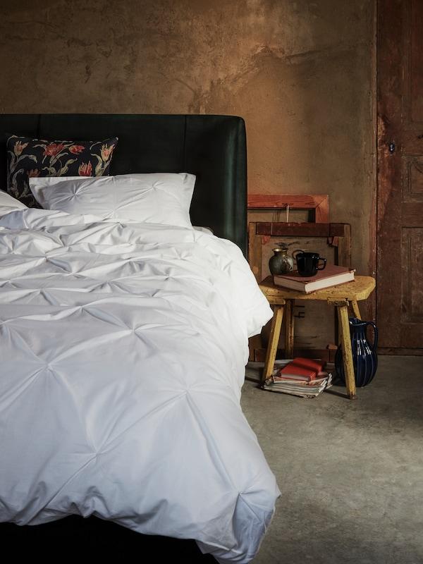 Makuuhuone jossa on vihreä TUFJORD-sänky. Sängyssä on ÅLANDSROT-koristetyyny sekä TRUBBTÅG-pussilakanat.