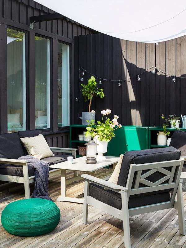 مساحةخارجيةبها كنبةBONDHOLMEN، وكراسي بذراعين وطاولة قهوة لون رمادي. بجوارها مقعد منخفض مستديرأخضرداكن.