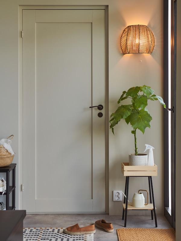Une applique MÅNALG allumée à côté d'une porte et au-dessus d'un meuble sur lequel repose une plante à grandes feuilles.