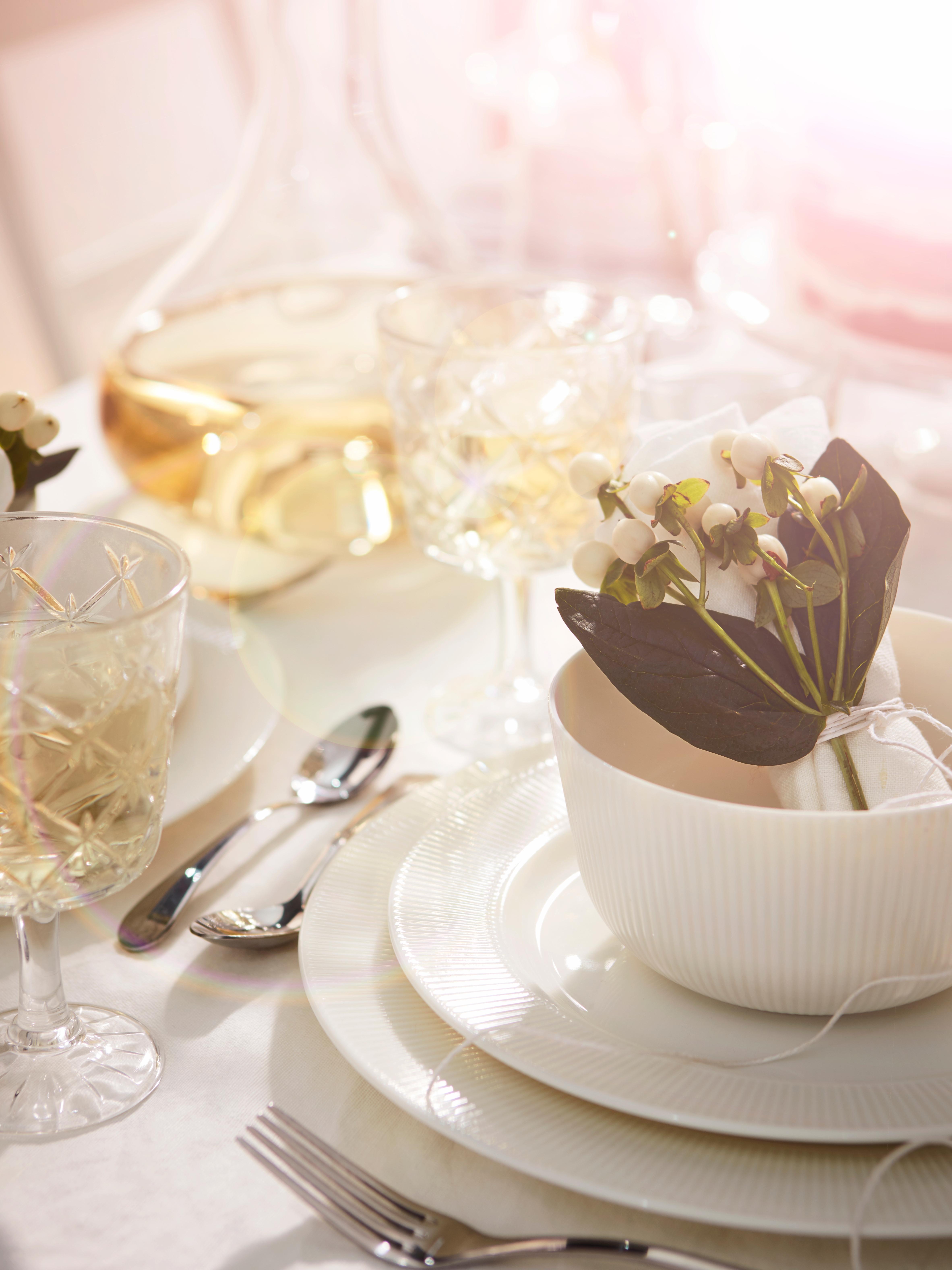 Bol OFANTLIGT blanc sur une table ensoleillée, préparée pour un repas avec une assiette standard et une petite assiette blanches et un verre transparent à motifs.