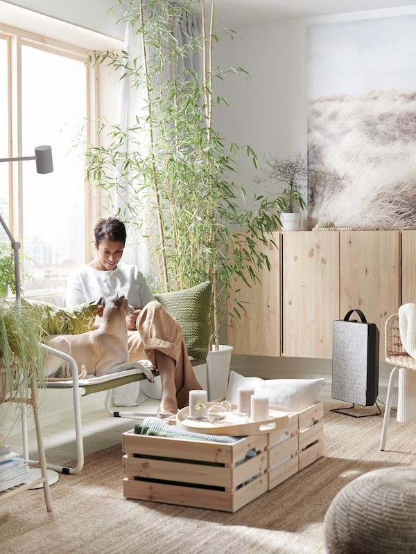 Eine Frau sitzt auf einem INGMARSÖ Sofa umgeben von einem Teppich aus Jute, einem Luftreiniger, luftreinigenden Gardinen und einem Tablett mit Duftkerzen.