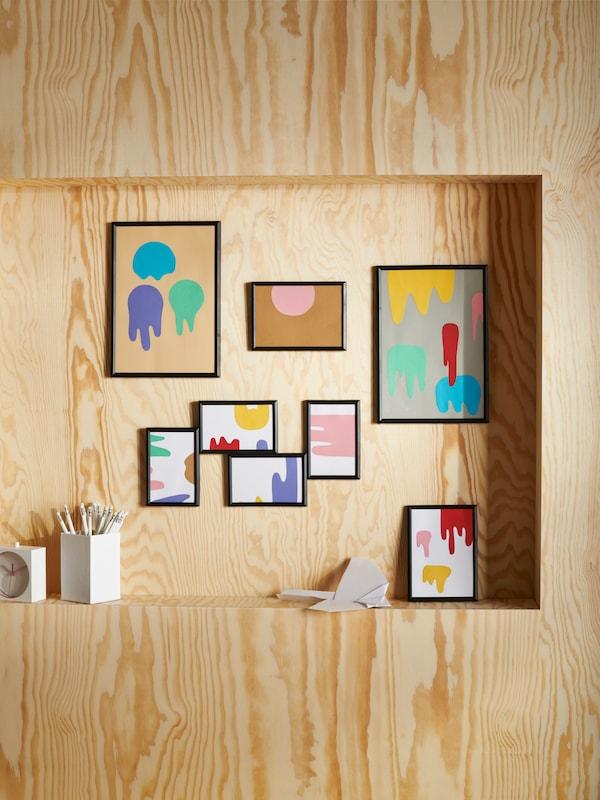 Verschiedene Bilderrahmen von IKEA an einer Holzwand
