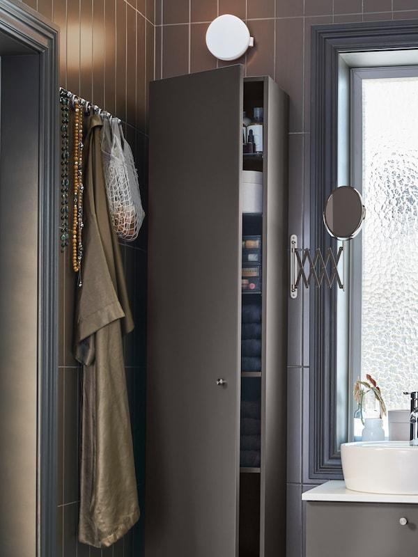 Armario alto gris escuro, espello redondo co brazo extensible e moble de soporte de lavabo en branco e gris escuro.