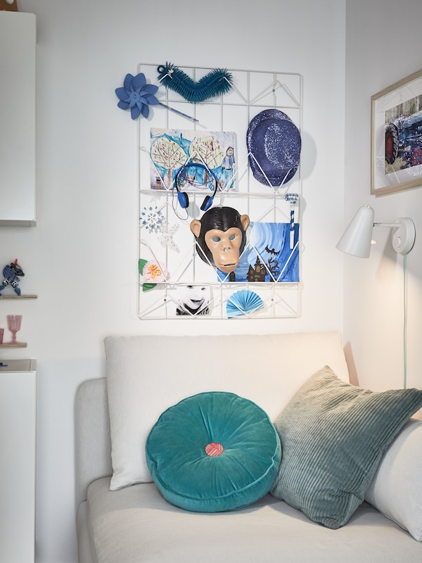 A white wired memo board with blue drawings and accessories, a beige sofa module, torquoise cushions, a white wall lamp.