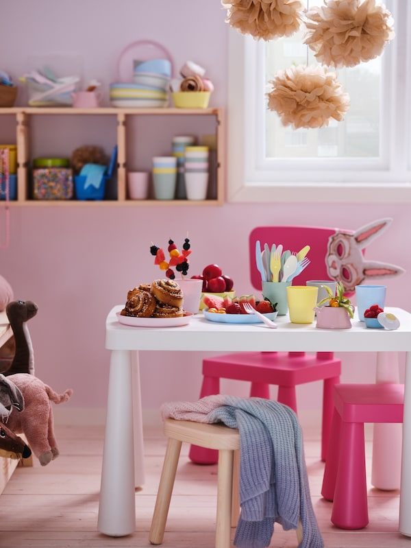 Pastelový pokoj s růžovými dětskými židlemi MAMMUT kolem bílého dětského stolu MAMMUT s barevným občerstvením.