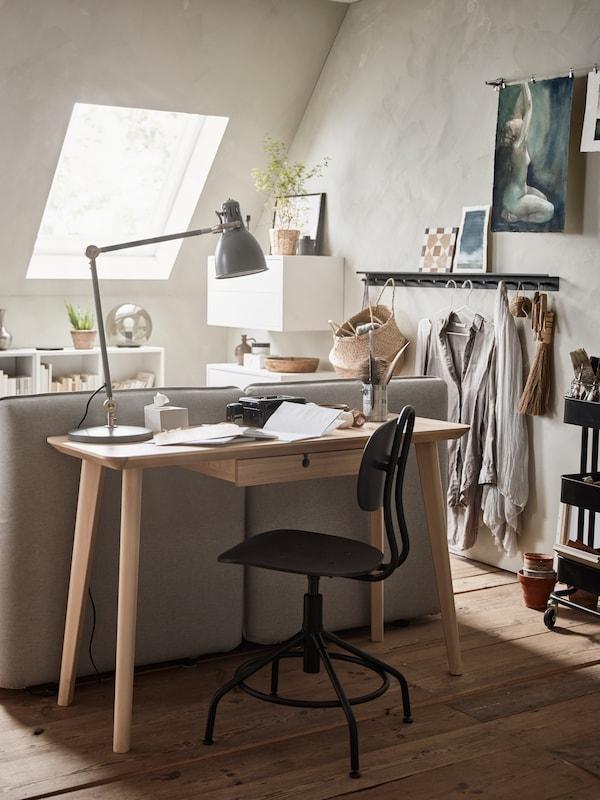 Del av rum syns där ett skrivbord står bakom en soffa. Rummet går i ljust och beiga färger.