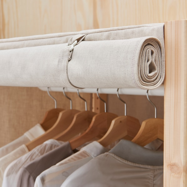 Part of an IVAR storage combination with clothes on hangers hanging from a clothes rail and a rolled-up fabric cover.