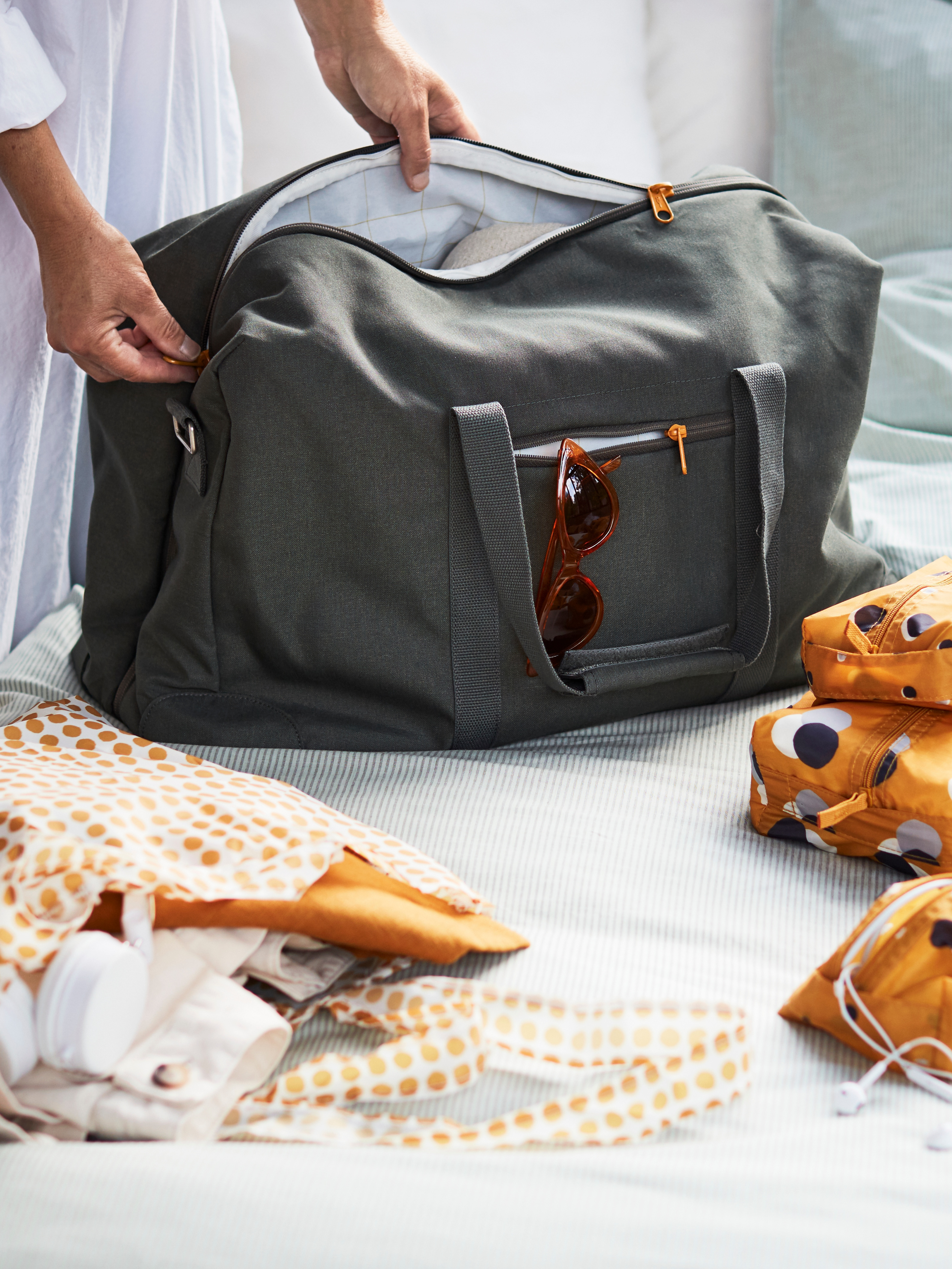 Sunglasses hang in a small pocket of an olive-green DRÖMSACK weekend bag being zipped open. It is on a bed with other bags.