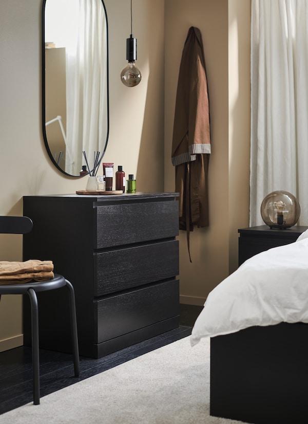 Cassetttiera MALM marrone-nero, 6 cassetti con sopra uno specchio ovale attaccato al muro.